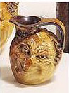 A Martin Brothers stoneware small double-sided face jug
